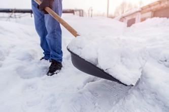 senior man shoveling snow with a large shovel