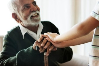 elderly man and his grandson touching hands