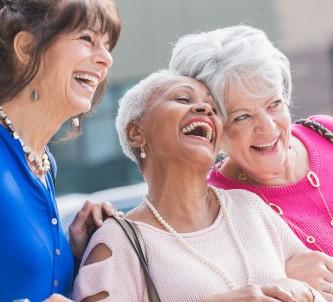 three senior women laughing and smiling