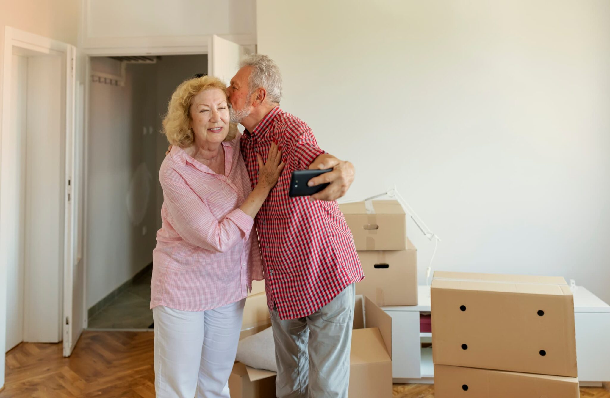 Older couple smiling and taking a selfie on move-in day with moving boxes in the background.