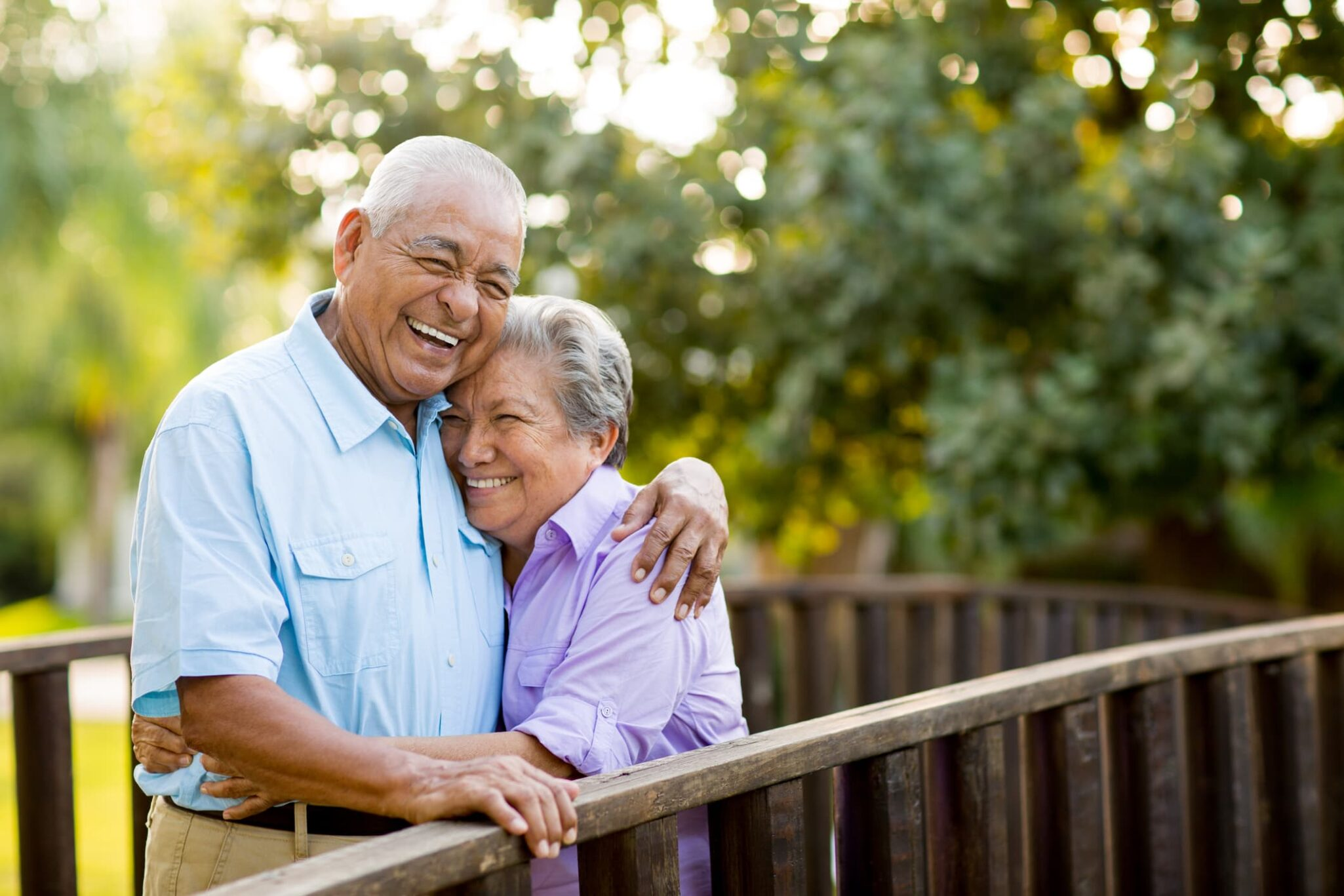 Older couple embracing on a bridge outdoors.