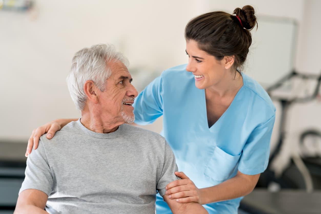 Older man smiling next to therapist.